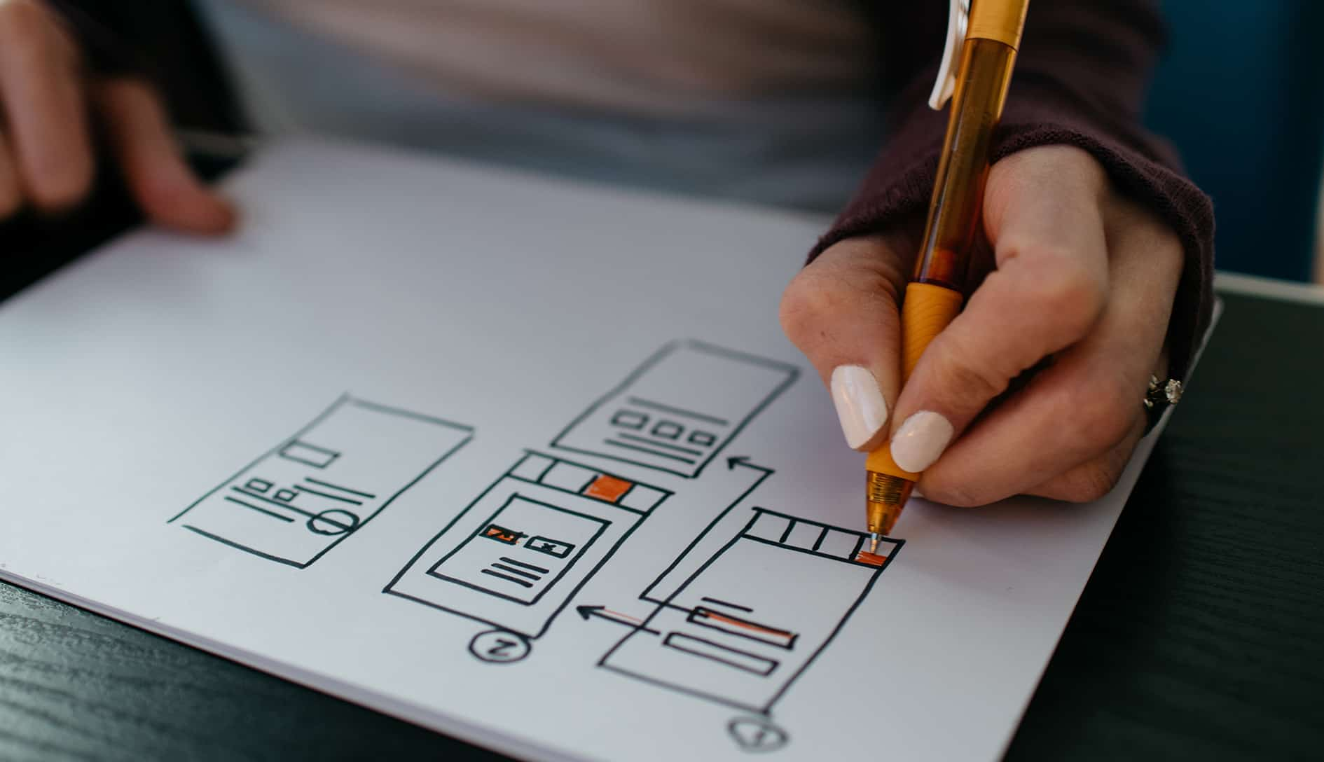 A hand holding a pen drawing mobile app designs for e-commerce on sheet of paper.